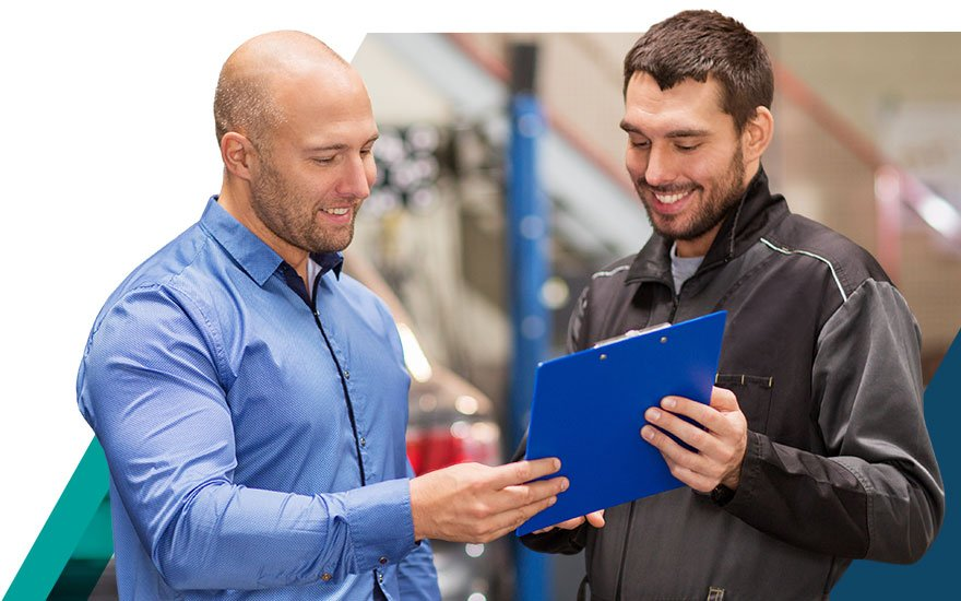 Fixed operations manager and automotive technician discussing performance data together