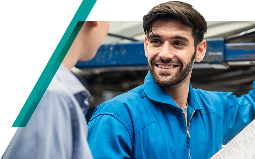 Handsome automotive technician looking satisfied and happy working in the service drive