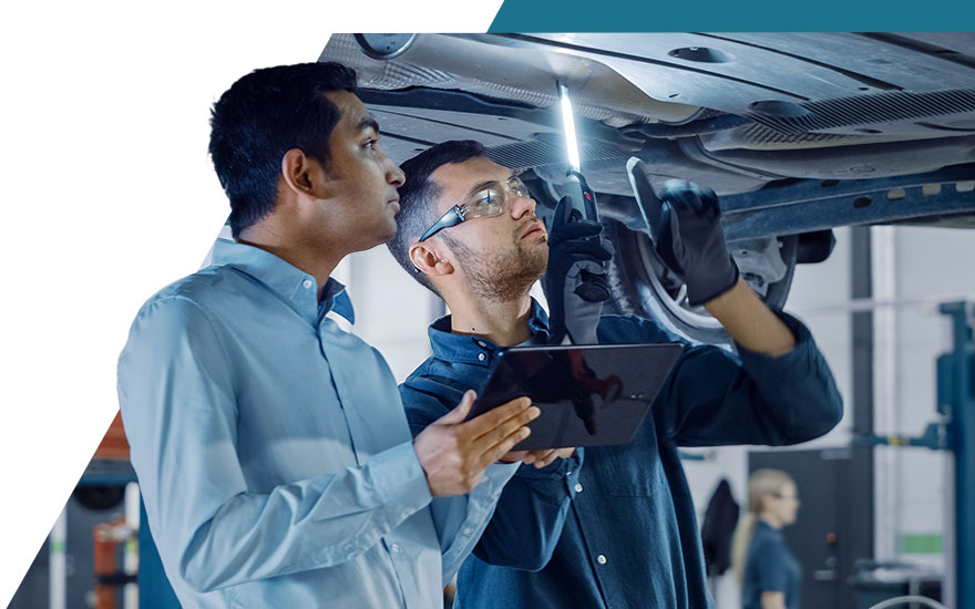 Automotive technician evaluating a vehicle while a consultant observes beside him