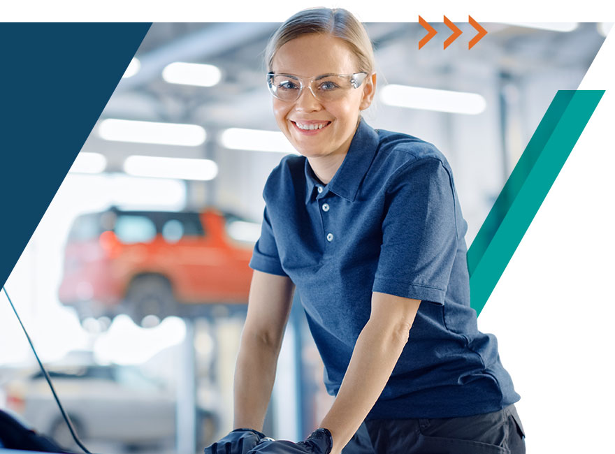 Beautiful auto technician looking satisfied and happy working in the service drive